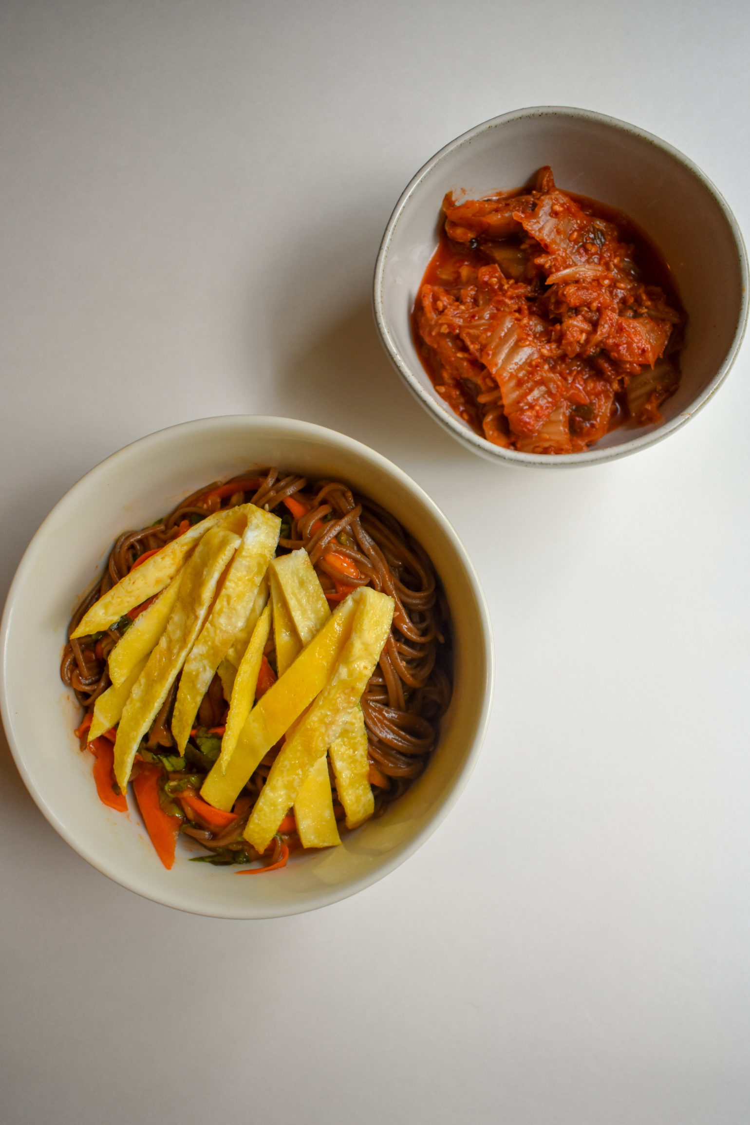 Korean cold spicy noodles with a side of kimchi